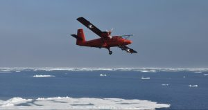 Twin Otter flying over ice and ocean