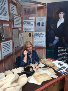 woman holding old fashioned phone whilst stat at desk in front of picture of Nancy Astor