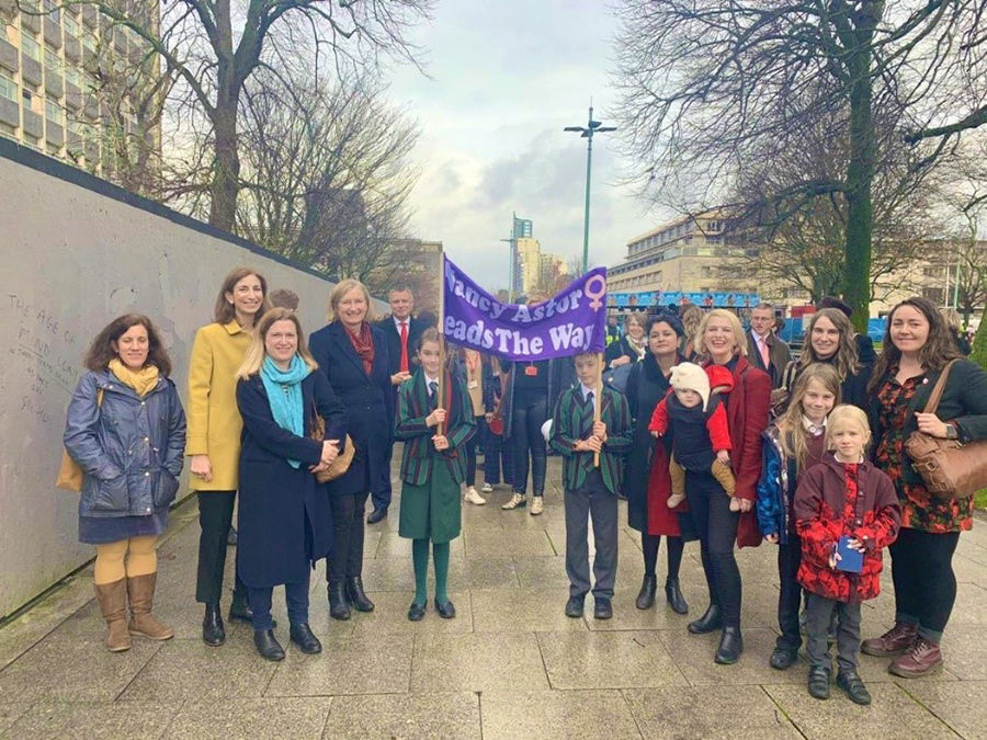 People on march with school children carrying banner