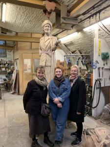 3 women standing in sculptor's studio with cast of Nancy Astor