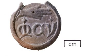 A terracotta medallion depicting Christ's hand, with abbreviated letters for 'Jesu Mercy' (© Glastonbury Abbey; photograph by David Cousins)