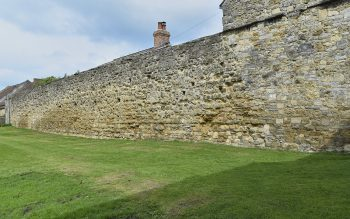 The north precinct wall at Glastonbury Abbey, with scars in the fabric suggesting the location of the former hostry (© Glastonbury Abbey; photograph: David Cousins)