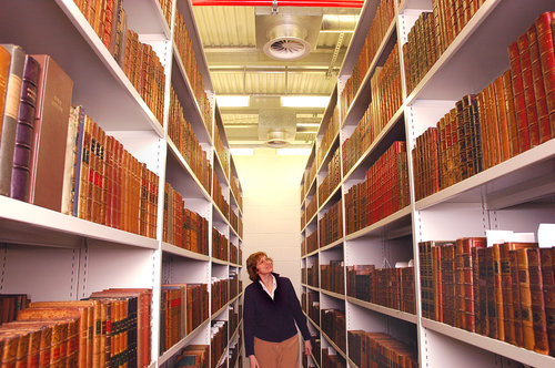volunteer looking at rows of bookcases
