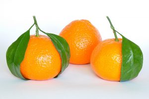 three mandarin oranges, two with stems and leaves attached