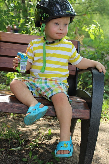Boy with Down Syndrome sitting on a bench.
