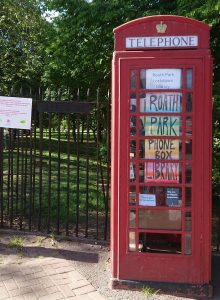 old red phone box with posters in windows