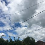 colour photograph of blue sky with white fluffy clouds