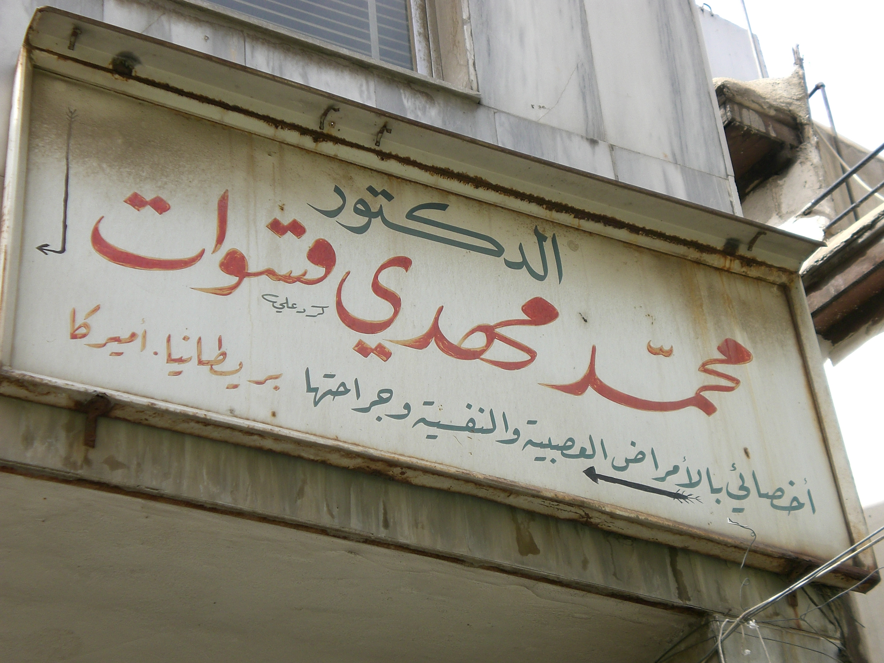 Hand-lettered shop sign of a doctor's surgery illustrating elongation principles of Arabic writing styles.